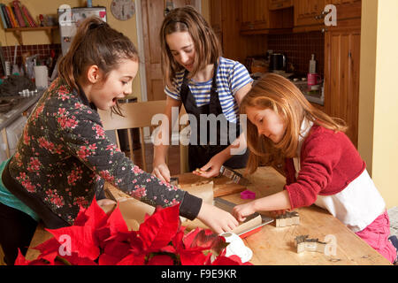 Working in a Small Space. Three sisters are working together in a small space to cut out gingerbread dough into - Stock Photo