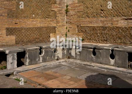 Latrine at the Domus of Triclini in the ancient Roman port of Ostia, near Rome, Italy, Europe - Stock Photo