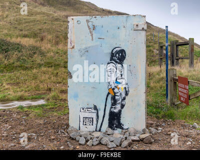 Graffito of a diver with a tank of sea air removed from a harbour wall during refurbishment re-erected as a piece - Stock Photo