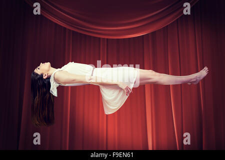 Composite image of girl in white dress floating in air