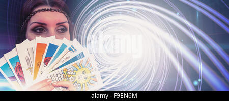 Composite image of fortune teller holding tarot cards while looking away - Stock Photo