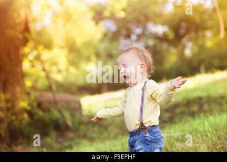 Little boy playing and having fun outside in a park - Stock Photo