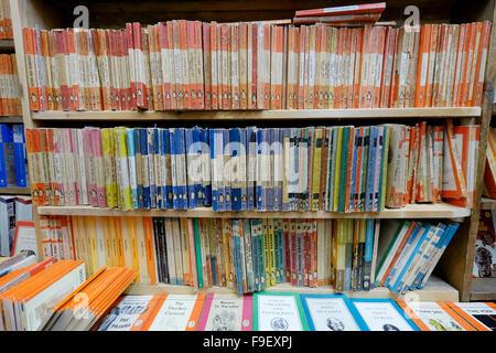 Three bookshelves of vintage Penguin paperbacks colour coded according to content e.g. orange for novels, blue for - Stock Photo
