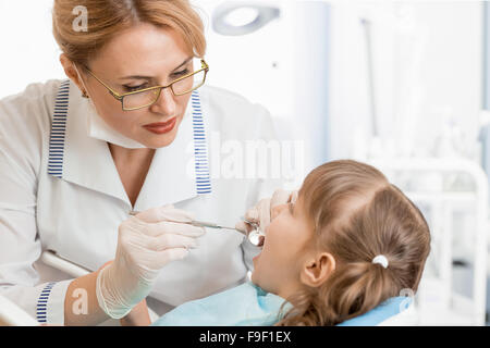 dentist woman examining kid patient in office - Stock Photo