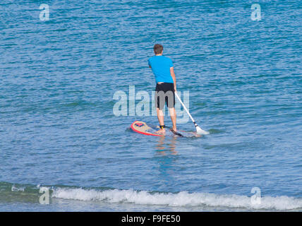 Caucasian Young Man Paddle Boarding in the Sea, UK - Stock Photo
