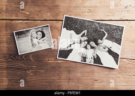 Black and white family photos laid on a table. Studio shot on wooden background. - Stock Photo