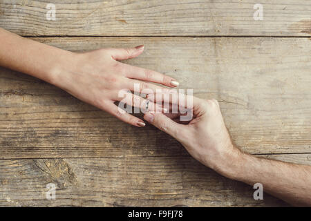 Man putting on engagement ring tenderly to his woman. Studio shot on a wooden background, view from above. - Stock Photo