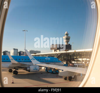 Schiphol Amsterdam Airport with KLM Cityhopper PH-EZO Embraer E-190 plane at the gate and control tower. View from - Stock Photo