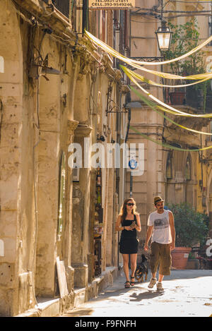 Young couple travel Italy, a young couple take a leisurely stroll through a street in the historic old town quarter of a southern Italian town. Stock Photo