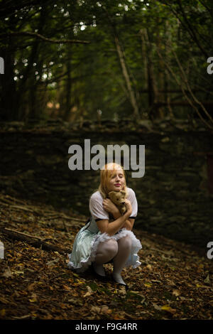 Malice in Wonderland / nightmare: a pretty blonde young woman girl wearing an 'Alice' type dress frock clutching - Stock Photo
