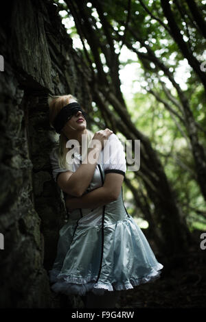 Malice in Wonderland / nightmare: a pretty blonde young woman girl, blindfolded,  wearing an 'Alice' type dress - Stock Photo