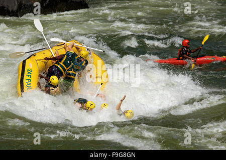 Rafters hit a wave and flip boat while rafting at the Boiling Pot on the Zambezi River, Zambia - Stock Photo