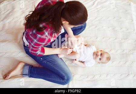 Cute little baby girl getting dressed by her mother on a carpet in a living room. - Stock Photo