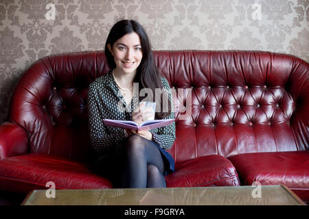 Young woman sitting on a sofa with a book and a drink - Stock Photo