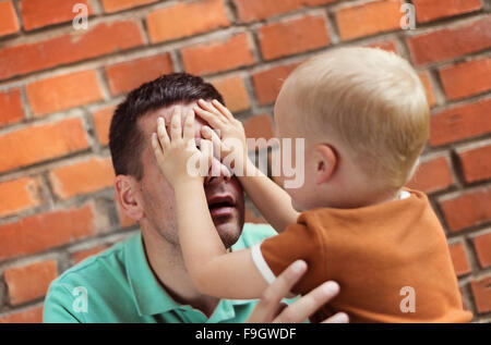 Father and son making funny faces together on a brick wall background - Stock Photo
