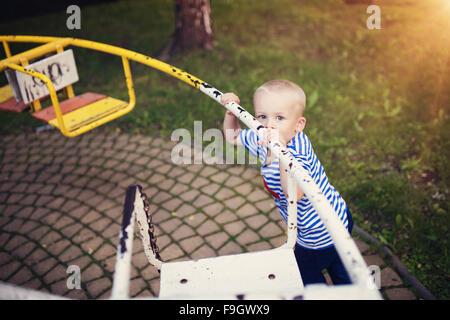Cute little boy in a park on an old carousel. - Stock Photo