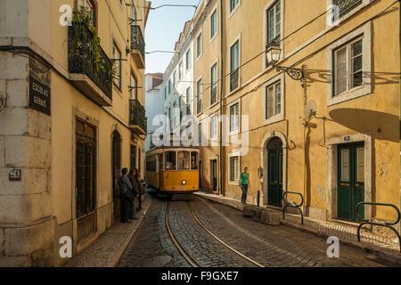 Traditional tram, 'Eléctrico', on a narrow street in Alfama, Lisbon. - Stock Photo