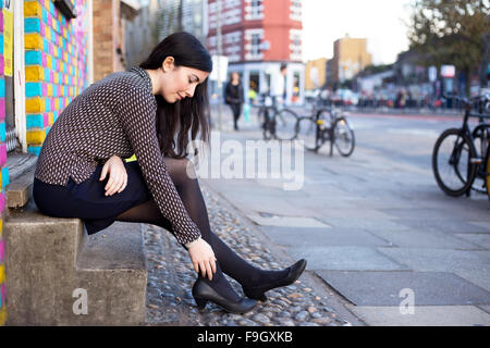 young woman in the street feeling pain in her ankle - Stock Photo