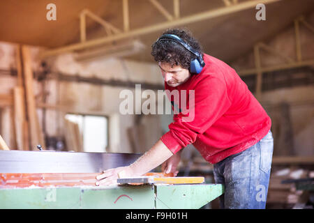 Carpenter working with electric wood planer in his workshop - Stock Photo