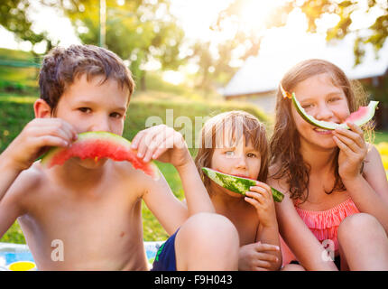 Beautiful kids eating watermelon outside in the garden - Stock Photo