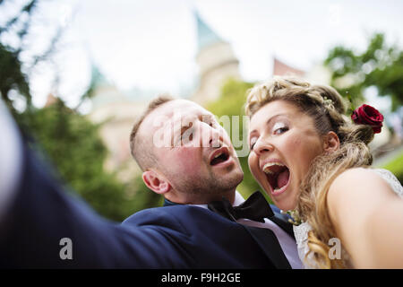Young wedding couple taking a selfie of themselves in front of a castle