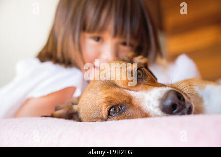 Toddler girl and her pet dog laying on the bed - Stock Photo