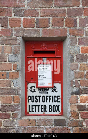 The Ludlow wallbox. A traditional British wall mounted red letterbox from the reign of George V. Moreton village, - Stock Photo
