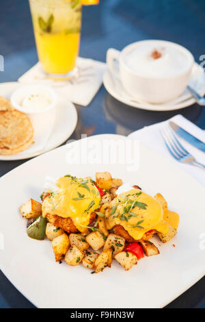 poached eggs and Dungeness crab cakes on breakfast potatoes, chipotle hollandaise, avocado and pico de gallo - Stock Photo