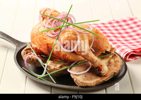 Roast chicken and potatoes on a skillet - Stock Photo