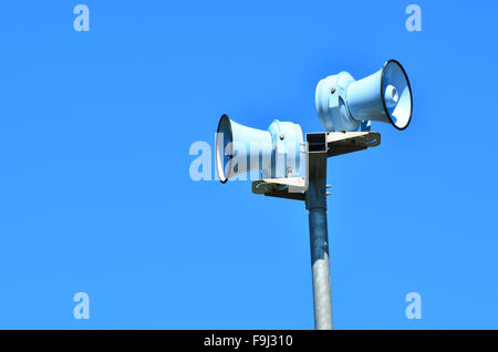 Air raid siren , against blue sky for emergency hazard of: tsunami, war, fire and flood. - Stock Photo