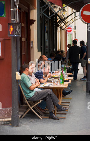 French people eating lunch at a typical Parisian street cafe on a narrow sidewalk - Stock Photo
