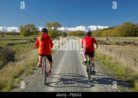 Cyclists on Otago Central Rail Trail in Ida Valley, and snow on Ida Range, Central Otago, South Island, New Zealand - Stock Photo