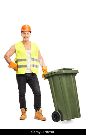 Full length portrait of a young male waste collector posing next to a green trash can isolated on white background - Stock Photo