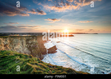 Stunning dramatic sunset from cliffs over Whipsiderry Beach at Porth in Newquay, Cornwall - Stock Photo