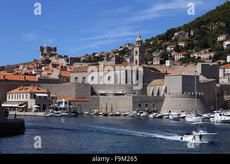 Small motor boat leaves the busy harbour at Dubrovnik, Croatia. City walls form a dramatic backdrop. - Stock Photo