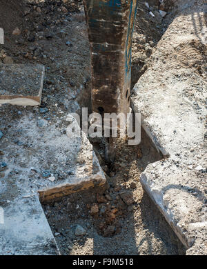 hammer hydraulic excavator performs the excavation for laying the broadband network with glass fibers - Stock Photo