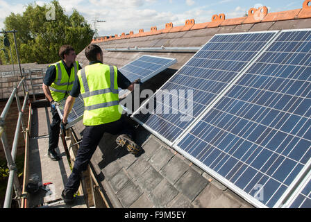 Workers install photovoltaic solar panels on the slate roof of a Victorian house in London, England. - Stock Photo