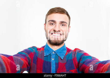 Selfie photo of happy smiling bearded young guy in plaid shirt - Stock Photo