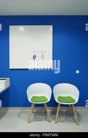 Waiting room in the children's centre at the Eye Hospital, Rotterdam, The Netherlands.  A bright blue wall. Two - Stock Photo