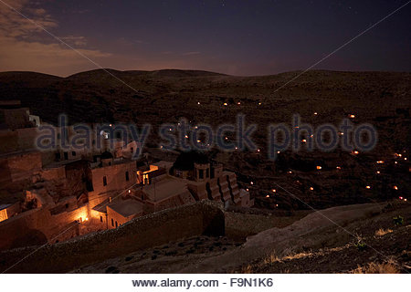 Light candles illuminating small caves near Mar Saba Monastery in the Judaean or Judean desert during Mar Saba Day - Stock Photo