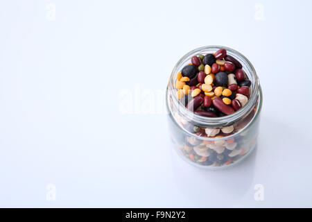 Mix bean of black eye peas, mung bean, adzuki beans, soy beans, black beans and red kidney beans in a mason jar - Stock Photo