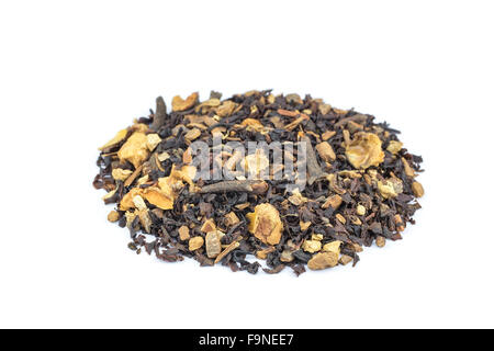 Biological mixed brown tea with herbs like cloves, apple and cinnamon isolated on white background - Stock Photo