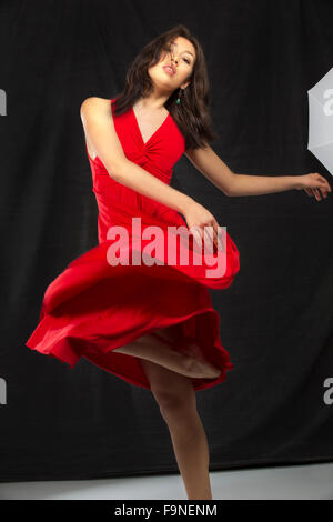 Young woman dancer in red dress in a modern dance turn, with black background and white floor, and part of a studio - Stock Photo