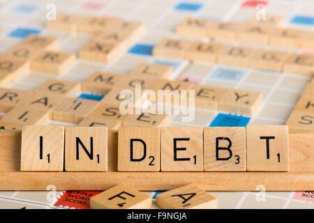 Scrabble - IN DEBT - Stock Photo
