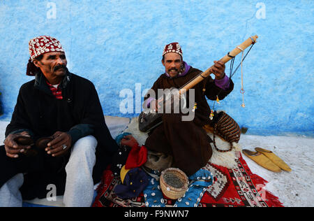 Gnawa musicians playing the Sintir and the Krakebs in the kasbah or Rabat. - Stock Photo