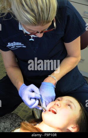 An orthodontist is a type of dentist who specializes in straightening crooked teeth. Adjusting braces and checking - Stock Photo