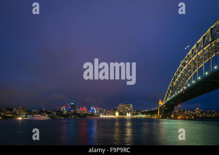Sydney, Australia - November 7, 2015: Night view of Luna Park and Sydney Harbour Bridge with office buildings in - Stock Photo