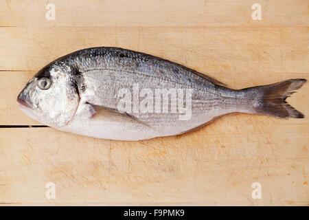Sea bream on wooden kitchen board. - Stock Photo