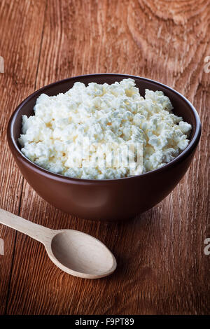 cottage cheese in a clay bowl on wooden table - Stock Photo