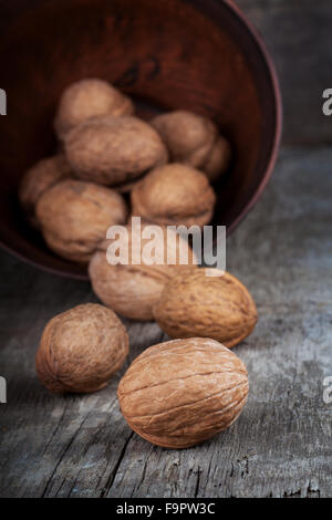 walnuts in clay bowl on wooden table - Stock Photo